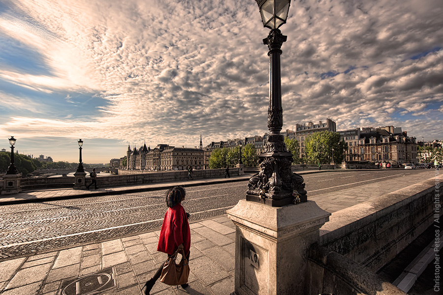 The Paris Pont Neuf bridge under morning light with a dramatic sky and clouds and an elegantly dressed woman in a red coat