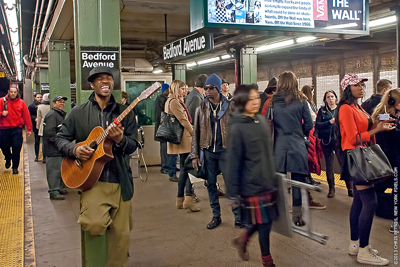 Musician and people in the Williamsburg train station.